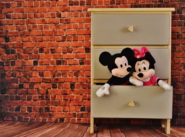 Komoda pro dětský pokoj s pootevřenou zásuvkou, z níž vykukují dva plyšáci