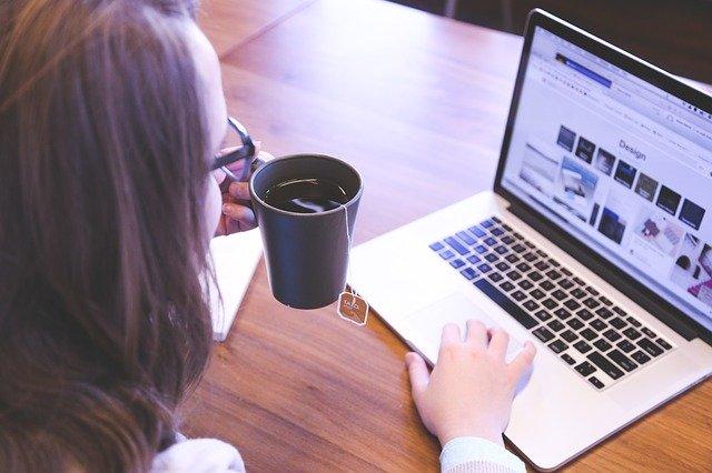 žena má čaj v ruce a pije a přitom se dívá na notebooku na web