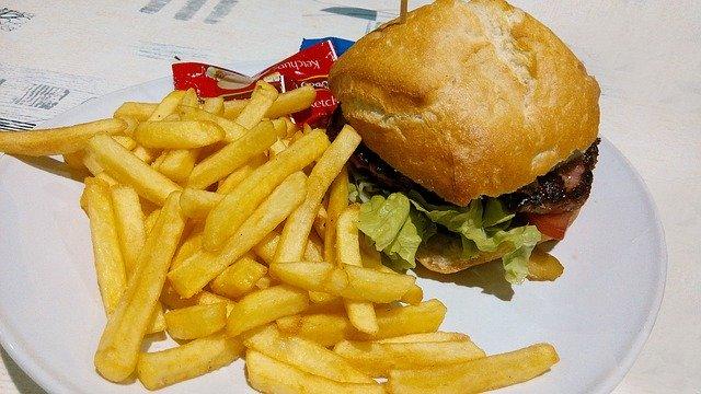 hamburger a hranolky na talíři s kečupem v malém plastovém pytlíčku.jpg