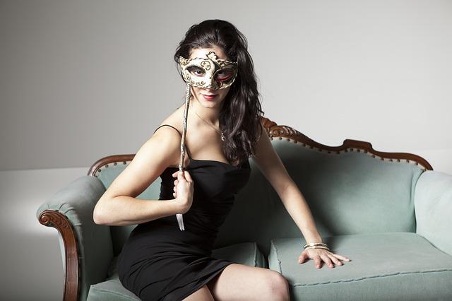 Žena ve společenských šatech držící si pře oči plesovou masku